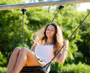 Smiling girl in skirt  on swing