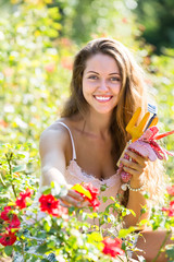 Girl in roses plant at garden