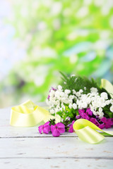 Flower wreath on white wooden table on green background