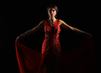 Young beauty woman in red dress. Isolated on black background