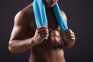 Athletic man holding a blue towel on black background