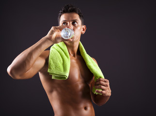 Fitness man drinking a bottle of fresh water on black background