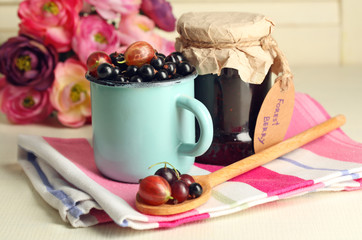 Ripe blackcurrants in mug and glass jar with tasty jam