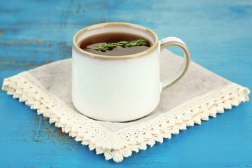 Cup of tasty herbal tea with thyme on blue wooden table