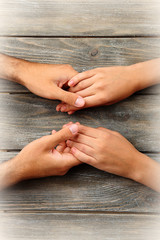Holding hands on wooden background