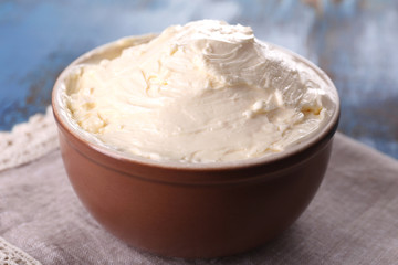 Fresh homemade butter in bowl, on color wooden background