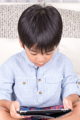 little boy playing with digital tablet
