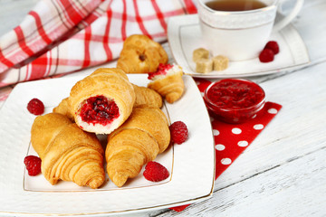 Breakfast with tea, jam and fresh croissants