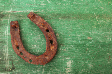 Old horse shoe on wooden background