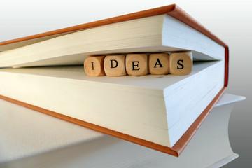 Ideas message written in wooden blocks between book pages