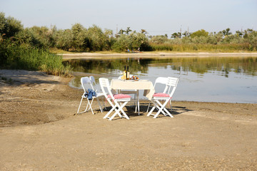 Table with dishware waiting for guests at beach of pond