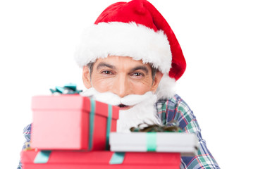 Man holding gifts and wearing santa hat. Isolated on white.