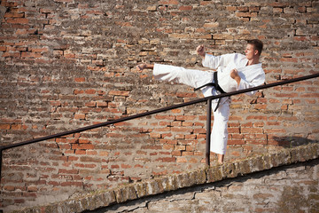 Young man practicing martial arts in front of a brick wall.