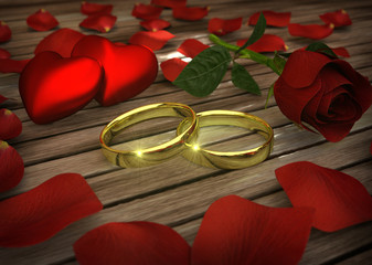Two golden wedding rings and red rose with petals