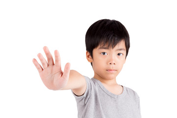 Portrait of a young boy making stop gesture on white background