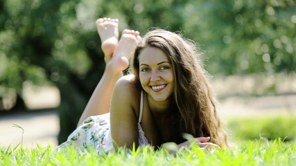 Smiling young woman  laying on meadow gras