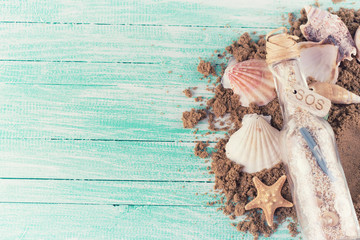 Marine items and sand on wooden background.