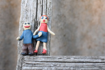 Funny plasticine man and woman on a wooden perch