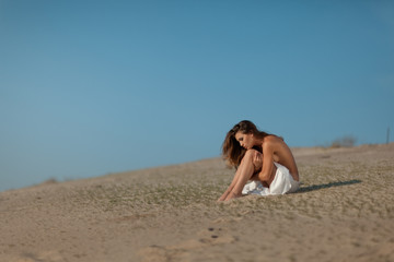 Girl sitting on the sand.