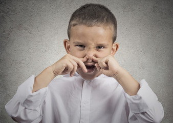 boy with disgust on face pinches nose something stinks