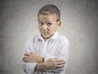 Child in awkward situation on grey wall background