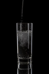 pouring mineral water in simple highball glass