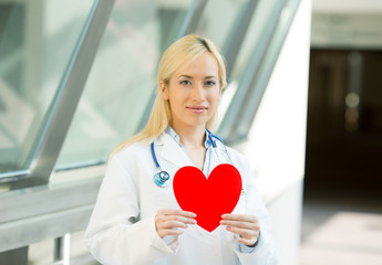 family doctor cardiologist holding red heart hospital hallway