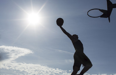 Basketball player silhouette slam dunking on a sunny day