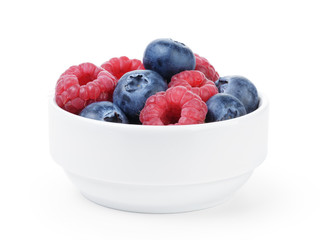 big ripe blueberries and raspberries in white bowl