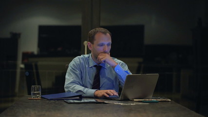 Young businessman working on laptop in the office at night