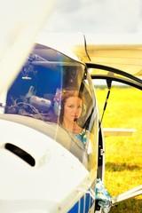 Beautiful woman in dress pilot in cockpit of ultralight plane