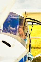 Beautiful woman in dress pilot in cockpit of ultralight plane