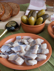 Herring, bread, pickles and bacon with plates on a green napkin