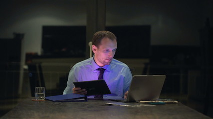 Businessman comparing data on laptop and tablet computer in the