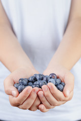 female teen hands holding ripe blueberries