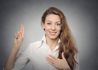 Happy attractive young woman giving a promise smiling