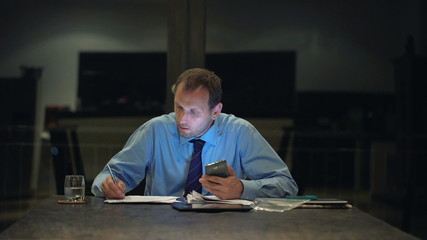 Businessman with smartphone, making notes in documents at night