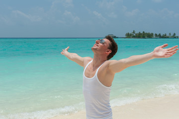 Man walking on the beach with open arms