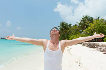 Man with open arms on the beach island
