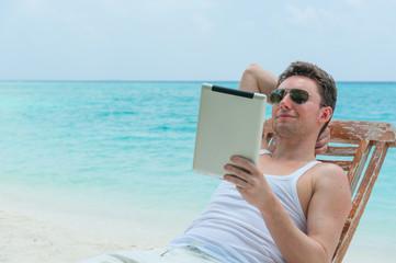 Man with tablet on beach