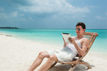 Man with tablet sitting on chair at the beach