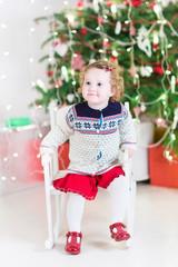 Beautiful girl in warm knitted jacket near Christmas tree