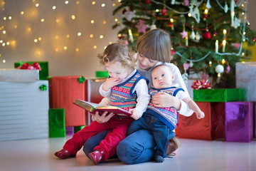 Cute happy boy reading to his siblings under Christmas tree