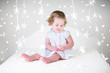 Leinwanddruck Bild - Cute curly toddler girl playing on bed between Christmas lights