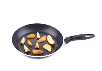 Fried potatoes on a black frying pan.