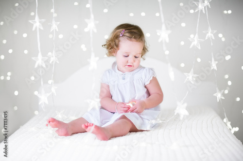 Leinwanddruck Bild Cute curly toddler girl playing on bed between Christmas lights