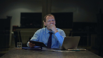 Overworked, tired businessman yawning in his office at night