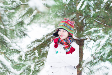 Portrait of a cute child playing in a snowy forest