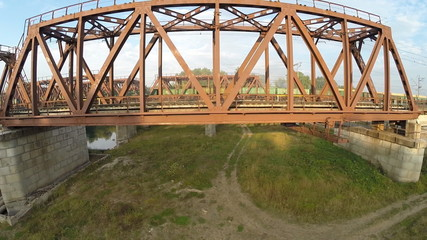Aerial view. Freight train traveling through the bridge. River