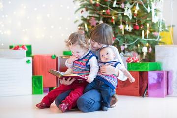 Portrait of thre kids under Christmas tree